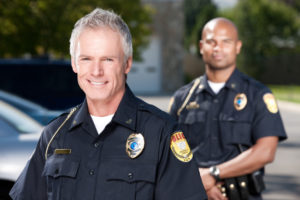 Head and shoulders portrait of a friendly law enforcement officer in his early 50s. His younger african american partner stands in the background behind him.